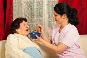 caregiver assisting senior woman in eating