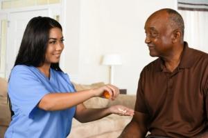 nurse giving medicine to elderly man