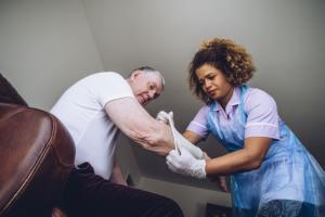 caregiver putting a bandage on senior man's arm